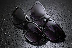 deux lunettes de soleil de paires avec des baisses de l'eau photos stock