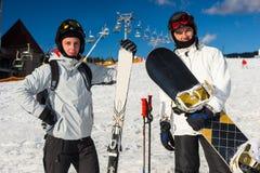 Deux mâles dans les ski-costumes, les casques et les lunettes de ski se tenant avec du Sn Image libre de droits