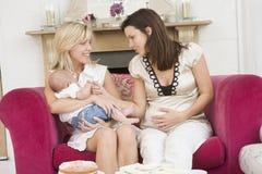 Deux mères dans la salle de séjour avec la chéri et le gâteau image libre de droits