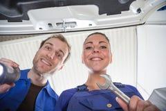 Deux mécaniques jetant un coup d'oeil sous le capot d'une voiture Image stock