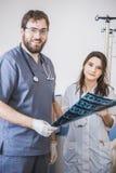 Deux médecins émettent la photo de rayon X du patient pour identifier le problème Conversation professionnelle, consultation des  Photographie stock