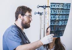 Deux médecins émettent la photo de rayon X du patient pour identifier le problème Conversation professionnelle, consultation des  Photos libres de droits