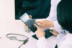 Deux médecins analysant et consultant au-dessus du disque médical en mode photos libres de droits