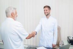 Deux médecins beaux se serrant la main dans l'armoire légère images libres de droits