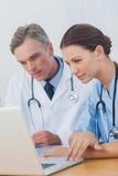 Deux médecins concentrés sur un écran d'ordinateur portable Photographie stock