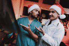 Deux médecins dans des chapeaux rouges avec le balayage de rayon X dans le bureau photo stock