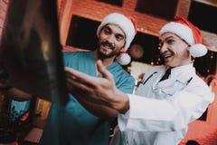 Deux médecins dans des chapeaux rouges avec le balayage de rayon X dans le bureau images libres de droits