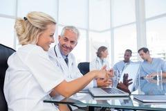 Deux médecins de sourire regardant un ordinateur portable Image libre de droits