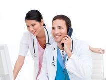 Deux médecins heureux parlant au téléphone Photo stock