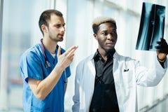 Deux médecins masculins de métis examinant le rayon X sur le bureau moderne de l'hôpital images stock