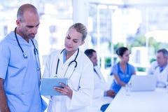 Deux médecins regardant le presse-papiers tandis que leur travailler de collègues photographie stock libre de droits