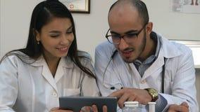 Deux médecins regardant quelque chose drôle sur le comprimé et rire photos libres de droits