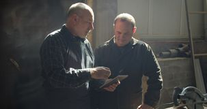 Deux maîtres de menuiserie se tenant dans la fabrication en bois discutant le processus observant dans le comprimé clips vidéos