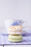 Deux macarons avec la tasse de thé sur la serviette de point de polka Photographie stock