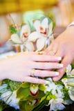 Deux mains avec des boucles de mariage sur le bouquet de fleur Photo stock