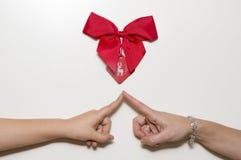 Deux mains avec des doigts touchant sous un ruban rouge Photographie stock libre de droits