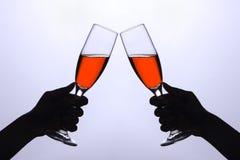 Deux mains avec des glaces de vin Photographie stock libre de droits