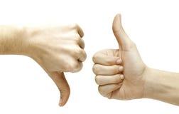 Deux mains avec des pouces en haut et en bas Images stock