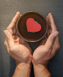 Deux mains avec le coeur de papier rouge dans une cuvette noire sur le panneau en bois Photographie stock
