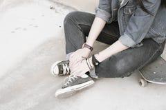 Deux mains avec le vintage adolescent de jeans et d'espadrilles dénomment, tiennent h Photo stock