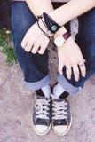 Deux mains avec le vintage adolescent de jeans et d'espadrilles dénomment, tiennent h Photographie stock