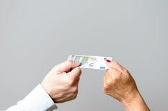 Deux mains conceptuelles tenant euro Bill dans la fin  Photographie stock libre de droits