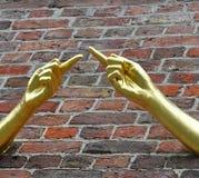 Deux mains d'or de pointage suggérant la connectivité et le respect mutuel images stock