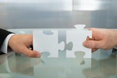 Deux mains d'homme d'affaires tenant le puzzle denteux Images libres de droits