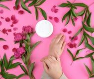 deux mains d'une jeune fille avec la peau lisse et d'un pot avec de la cr?me ?paisse et les pivoines fleurissantes de Bourgogne photographie stock