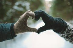 Deux mains dans les gants tenant le symbole de coeur d'amour Photo libre de droits