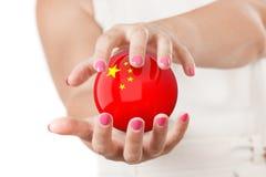 Deux mains de femme protégeant la sphère de globe de la terre de drapeau de la Chine Photos libres de droits
