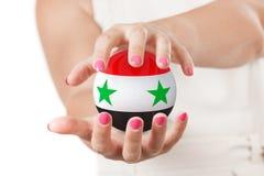 Deux mains de femme protégeant la sphère de globe de la terre de drapeau de la Syrie Images libres de droits