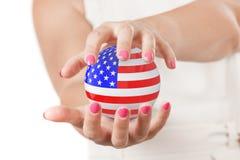 Deux mains de femme protégeant la sphère de globe de la terre de drapeau des Etats-Unis Photo stock