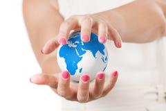 Deux mains de femme protégeant le globe de la terre de planète Photographie stock