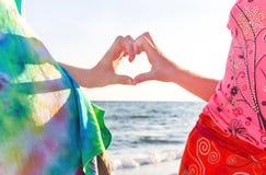 Deux mains de garçon et de fille (adolescents) dans la forme du coeur Photographie stock