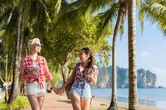 Deux mains de prise de femme marchant en parc tropical de palmiers sur la plage, beau jeune couple femelle des vacances d'été Photo stock