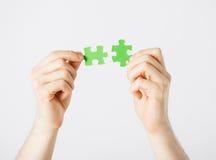 Deux mains essayant de relier des morceaux de puzzle Photographie stock libre de droits