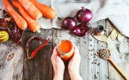 Deux mains femelles jugeant un pot avec un verre de carotte fraîche juic photographie stock