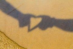 Deux mains formant un symbole d'ombre ou d'amour de coeur sur la plage Temps de vacances Temps de vacances Images libres de droits