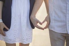 Deux mains forment une forme de coeur avec leurs doigts, la fille est habillée dans un bain de soleil, le type est habillé en jea Photos stock