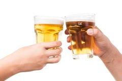 Deux mains grillant la bière froide régénératrice Image stock