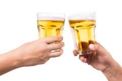 Deux mains grillant la bière froide régénératrice Photographie stock