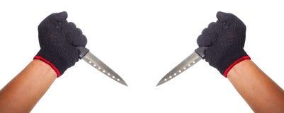 Deux mains jugeant des couteaux prête à cuisiner ou la mise à mort Image libre de droits