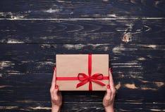 Deux mains jugent un boîte-cadeau intéressant attaché avec le ruban rouge Photographie stock libre de droits