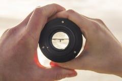 Deux mains, mâle et femelle tenant un objectif de caméra, par le le photographie stock libre de droits