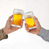 Deux mains masculines dans des chemises tiennent les téléphones intelligents avec de la bière sur le fond blanc Images stock