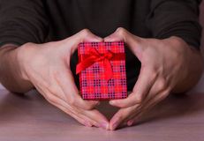 Deux mains masculines dans la forme du coeur tenant le boîte-cadeau à carreaux rouge Photographie stock