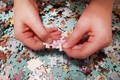 Deux mains prennent des puzzles images stock
