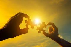 Deux mains relient deux pièces du puzzle contre le ciel et l'éclat du soleil au coucher du soleil photographie stock libre de droits