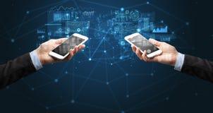 Deux mains tenant des smartphones sur des données commerciales de synchronisation image stock